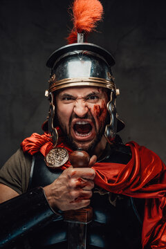 Savage and armoured roman soldier with red cloak screaming staring at camera holding a sword in dark background.