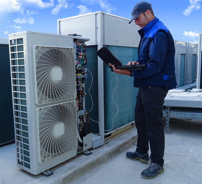 air conditioning technician making a diagnosis of an industrial air conditioning unit with a laptop next to other VRV condenser units on a rooftop in a sunny day