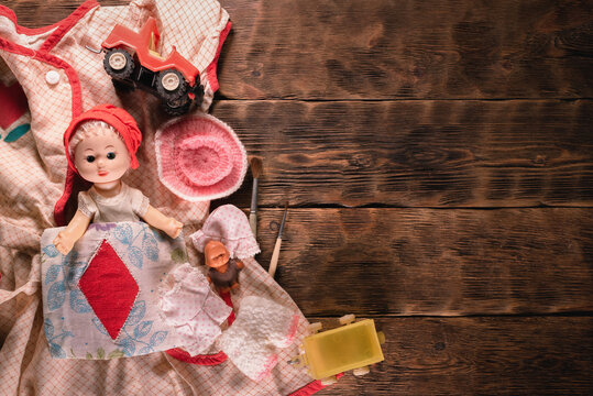 Old retro girl children toys on the brown wooden table background.