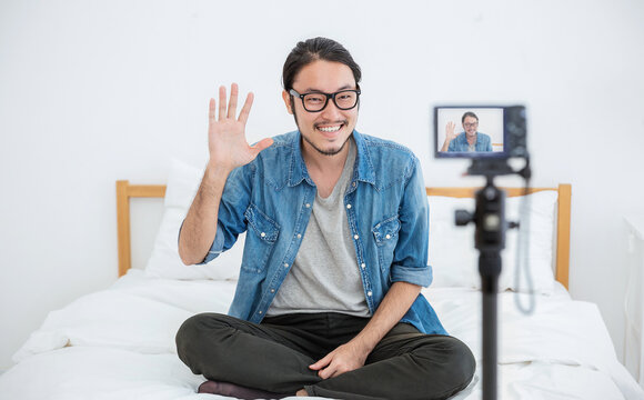 Portrait of small business owner sme vlogger man, video online marketing live in camera. Young asian guy say hi to social network. SME entrepreneur blogger online business concept