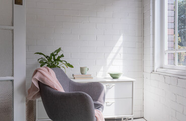 Sunroom with grey chair, white sideboard, painted brick walls and copy space (selective focus)