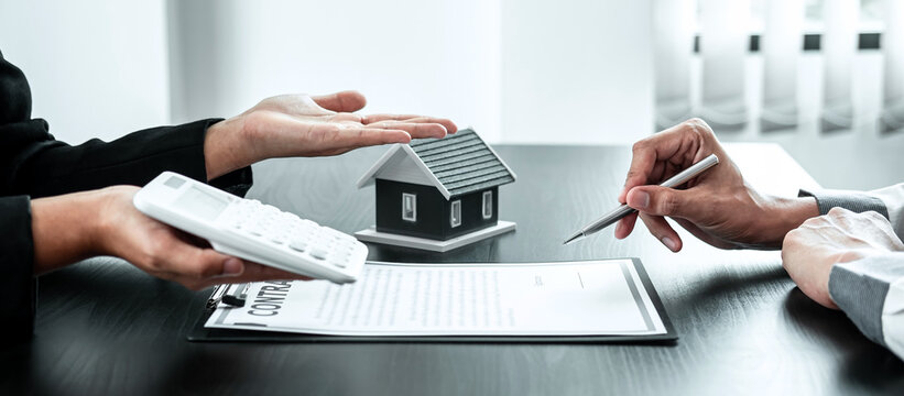 Estate agent are presenting home loan to client and discussing to decision signing agreement contract form, Home Insurance and Real estate investment concept