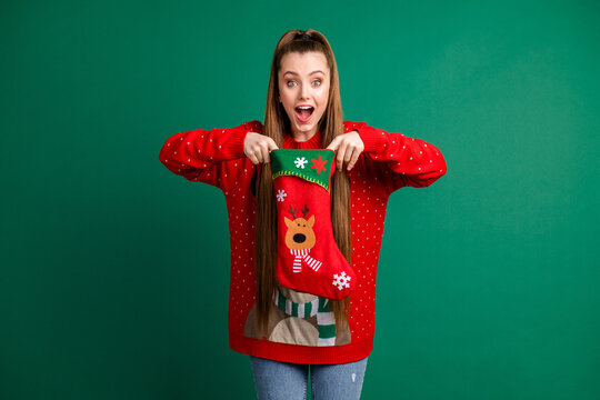Photo of attractive funny excited lady hold newyear stocking x-mas morning waiting present family tradition look inside wear red ugly ornament pullover isolated green color background