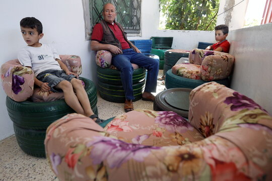 A man sits with his children on seats made by Abdullah al Momani at their home in Ajloun