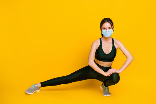 Full length body of cheerful strong girl doing physical exercise training wear mask isolated on bright yellow color background