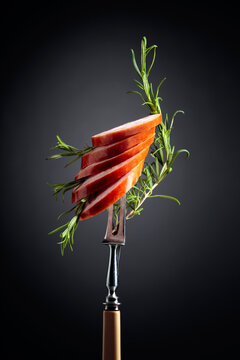 Sliced sausage with rosemary.