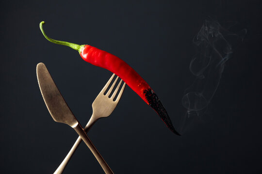 Hot chili red pepper smoking on a fork. Spice concept.