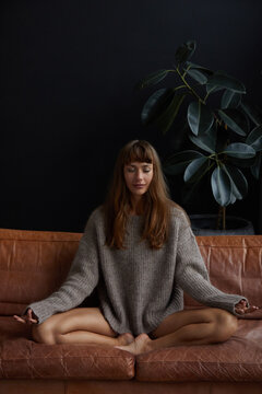Young woman meditating on a leather sofa