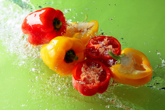 Red and yellow paprika in water splashes.