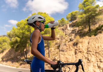 Young boy drinking water and energetic drink and holding bike after cycling outside on the road