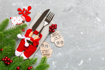 Wall Mural - Top view of holiday objects on cement background. Utensils tied up with ribbon on napkin. Christmas decorations and reindeer with copy space. New year dinner concept