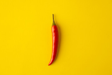 spicy red chili pepper on yellow background