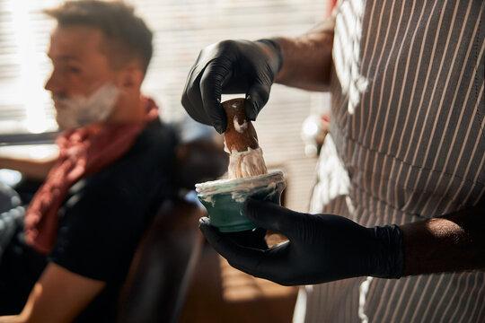 Male barber lathering shaving cream with brush