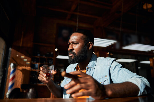 Handsome Afro American man smoking cigar and drinking whisky