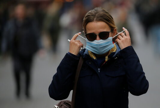 A woman adjusts her protective face mask as she walks along a street in Kyiv