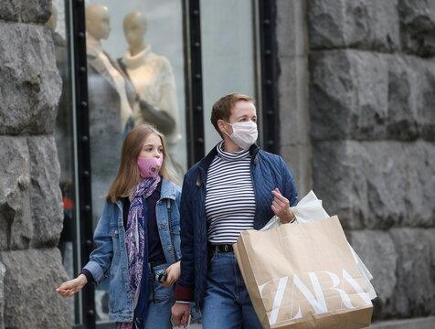 Women wearing protective face masks walk along a street in Kyiv