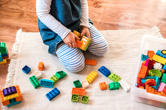 Little girl playing with her colorful blocks.
