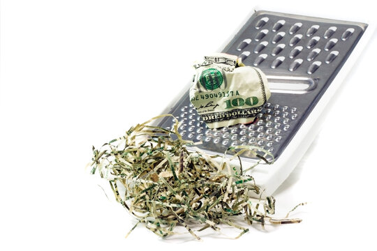 Crumpled hundred dollar being shredded on cheese grater.