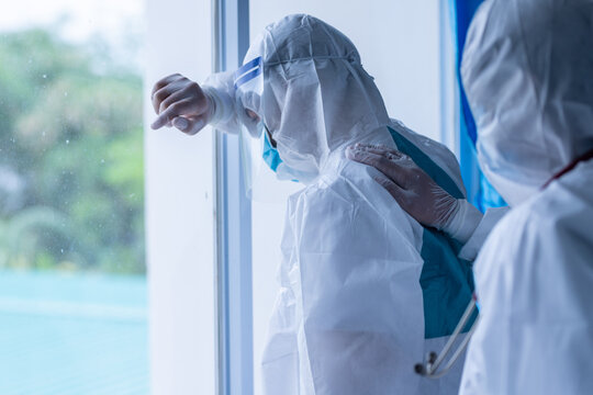 Tired depressed doctor wear PPE feels desperate thinking of medical problem feels burnout of second-round spread of coronavirus in hospital