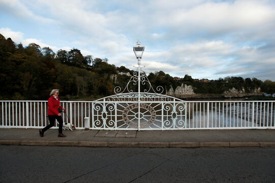 A woman walks her dog at the bridge over the River Wye between Chepstow, in Monmouthshire, Wales and Tutshill, Gloucestershire, Britain
