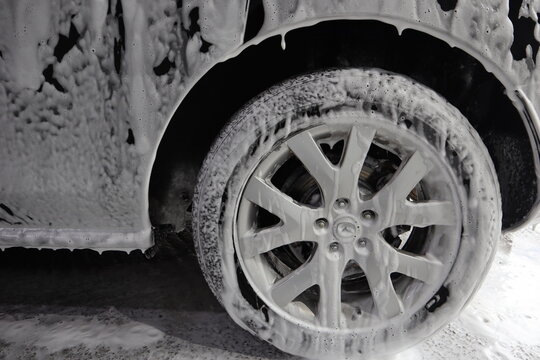 car wheel is covered with soapy foam
