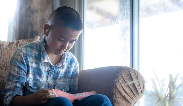 Boy readinh Bible on sofa at home, Religion concept.
