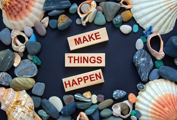 Text 'make things happen' on wooden blocks on a beautiful black background. Sea stones and seashells. Concept.
