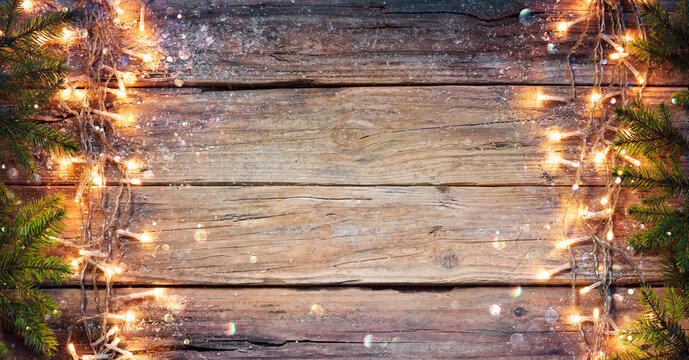 Rustic Christmas Border - Fir Branches And String Light On Old Wooden Plank With Defocused Abstract Bokeh