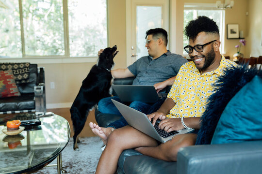 Happy gay couple working from home with laptops on couch with their Australian Shepherd
