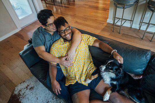 Gay male couple snuggling at home on couch together with their Australian Shepherd dog