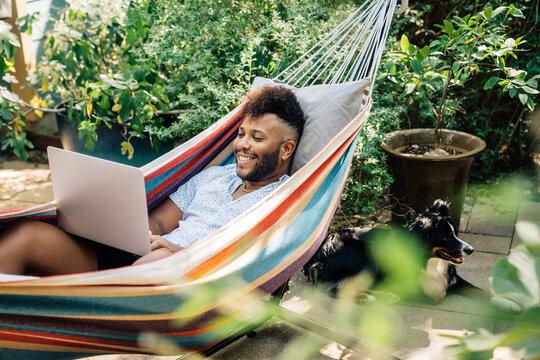 Man relaxing in hammock working on laptop computer