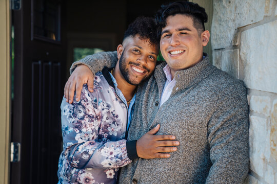 Portrait of happy, smiling gay male couple hugging in doorway of home