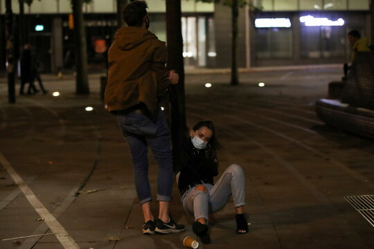 A man helps lift a woman off the ground the night before a local lockdown amidst the spread of the coronavirus disease (COVID-19) in Manchester