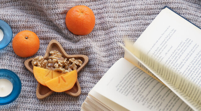 Winter cozy environment flat lay orange mandarins, candle, nuts, soft knitted background
