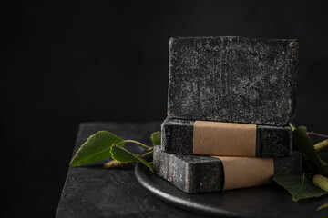 Wall Mural - Stack of natural tar soap on black table