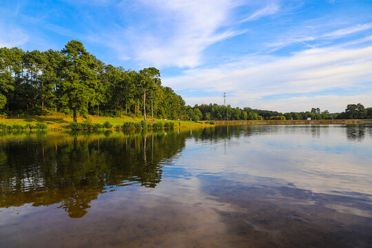 stunning shot of the still lakes waters with lush green and autumn colored trees and blue sky and clouds reflecting off the lake at Rhodes Jordan Park at Lawrenceville Lake in Lawrenceville, Georgia