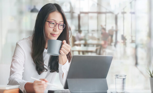 Young asian woman drinking and relaxing while working at office.