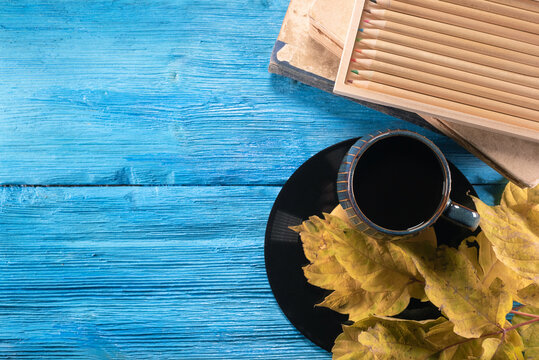 Black coffee cup, pencils, books and fallen maple leaves on the blue table. Autumn background with copy space. Education background.