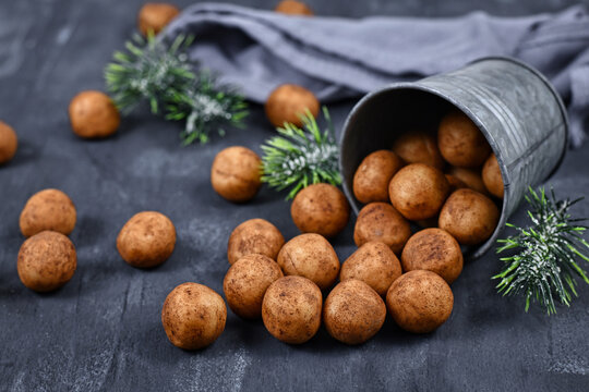 German traditional Christmas sweets called 'Marzipankartoffeln'. Round ball shaped almond paste pieces covered in cinnamon and cocoa powder spilling out of iron cup on dark background