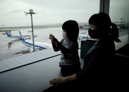 A family members wearing protective face masks watch airplanes, amid the coronavirus disease (COVID-19) outbreak, at Haneda Airport in Tokyo