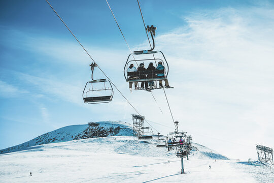 People on ski lift in winter ski resort  - Focus on guys sitting in cable car
