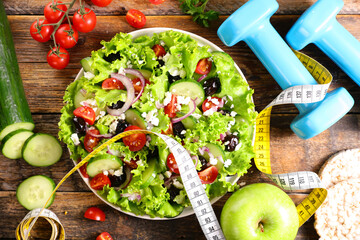 diet food concept- vegetable salad with dumbbell and meter