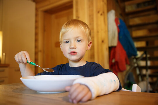 Little boy with a broken wrist eating at the table. Boy with a plaster on his arm.