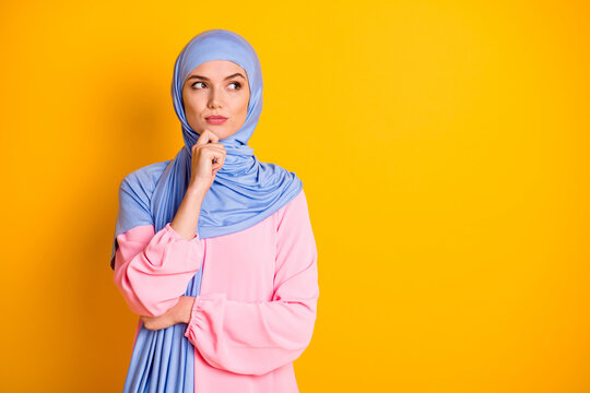Portrait of attractive minded smart clever muslimah wearing hijab thinking isolated over bright yellow color background