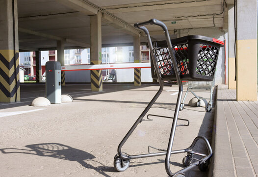 A single shopping cart in the parking lot. Shopping cart in a store parking lot