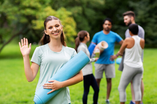fitness, sport and healthy lifestyle concept - happy smiling young woman with mat waving hand over group of people meeting for yoga class at summer park
