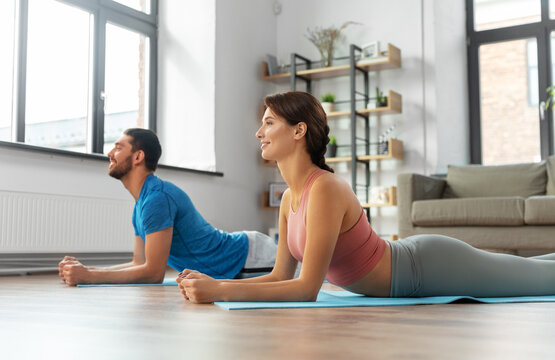 sport, fitness, lifestyle and people concept - smiling man and woman exercising at home