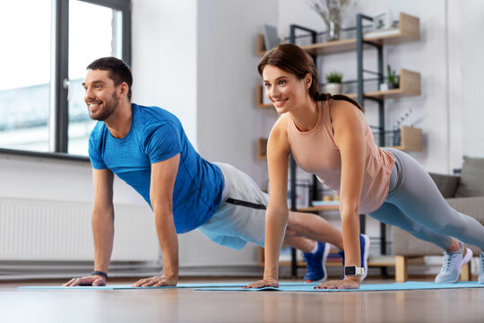 sport, fitness, lifestyle and people concept - smiling man and woman exercising and doing plank at home