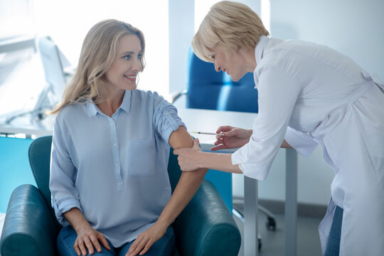 Blonde female doctor making injection into arm of smiling female patient
