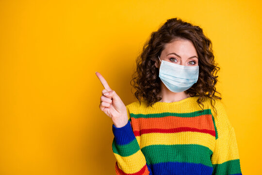 Photo portrait of woman pointing one finger at blank space wear medical mask isolated on bright yellow colored background